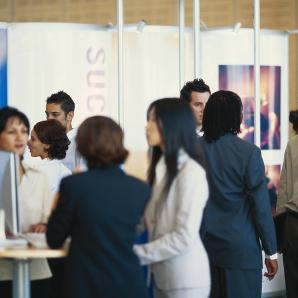 Internationale Geschäftsleute in einer Messehalle.