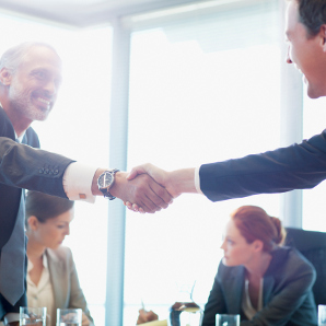 Zwei Männer schütteln sich die Hände über einem Konferenztisch.