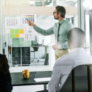 Ein Mann zeigt seinen Kollegen Strategiepläne an der Wand.