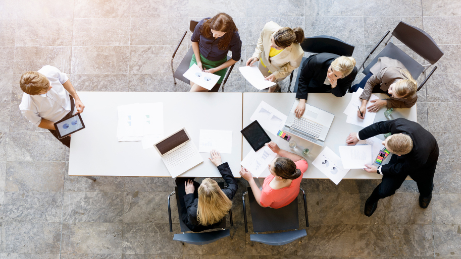 Blick von oben auf Kollegen am Konferenztisch bei einem Geschäftsmeeting.