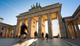 Fußgänger und Radfahrer am Brandenburger Tor in Berlin.