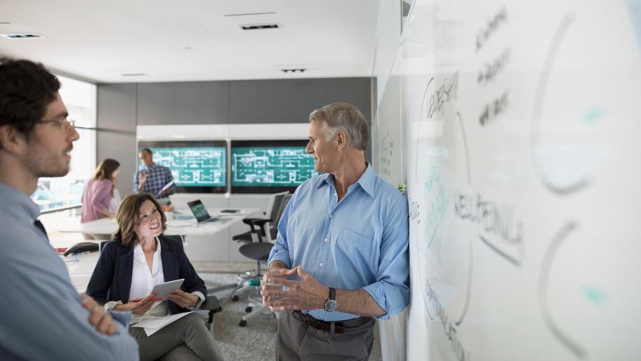 Kollegen beraten sich an einem Whiteboard im Büro.