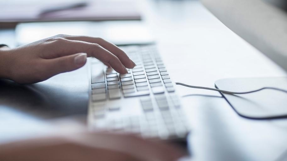 Nahaufnahme einer Frau mit Tastatur und Computermaus.