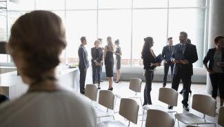 Menschen stehen miteinander sprechend bei einer Konferenz.