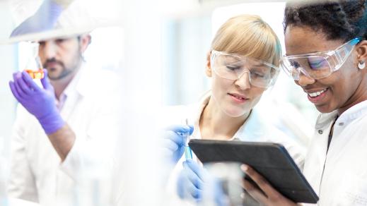 Laboranten betrachten einen Tablet-PC.