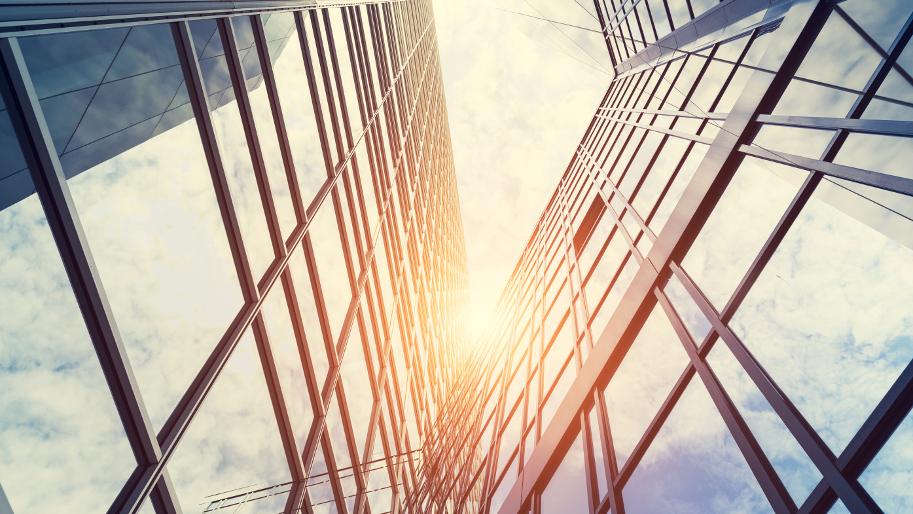 Sonnenbeschienene Glasaußenfront zweier Gebäude.